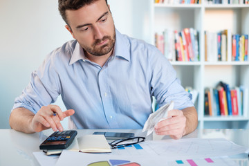Businessperson sitting in office and using calculator