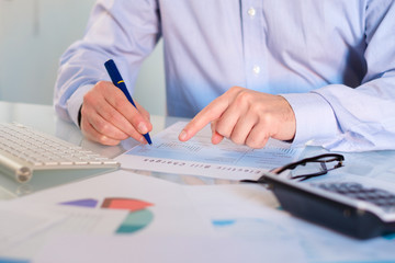 Close-up of businessperson analyzing accounting document at desk in office