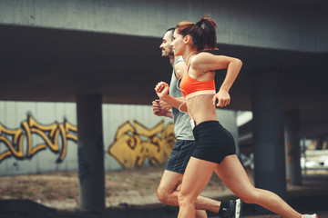 Couple of runners jogging on the city street .City environment.