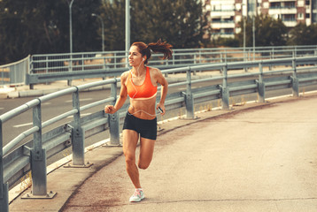 Female runner jogging on the city street by the traffic road.City environment.