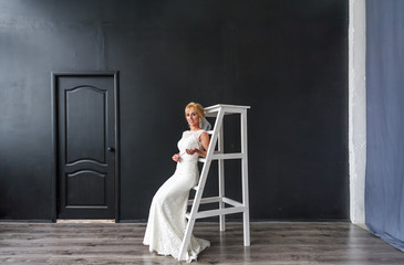 Beautiful young woman blonde bride on the wooden stairs in the interior in studio