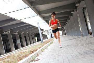 Female runner jogging under the traffic overpass.City environment.