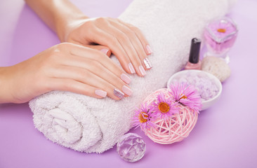 Beautiful pink and silver manicure with flowers and spa essentials