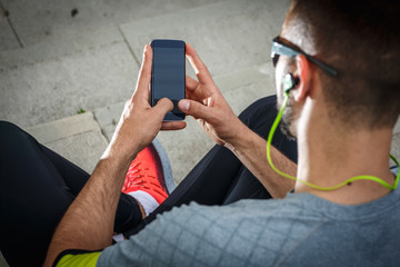 Man relaxing after jogging.He using his smart phone and listening to music.