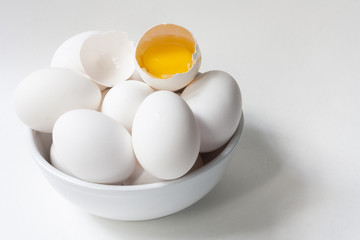 Eggs and yolk in white bowl on white background with copy space
