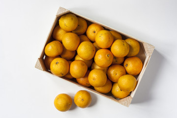 Box of clementines on white background top view