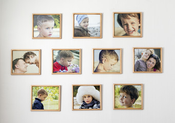 White wall with photos of the family in photo frames. Kid room concept.