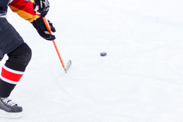 Ice hockey player with stick hitting the puck on rink