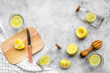 Prepare refreshing beverage lemonade. Lemons, juicer, bottle, knife, cutting board on grey stone background top view copyspace