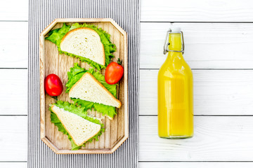 Sandwiches with lettuce and tomatoes for picnic on tablecloth on white wooden background top view
