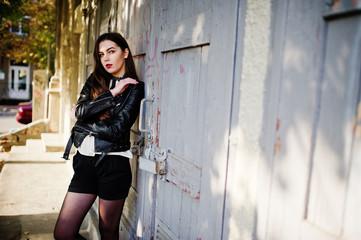 Stylish brunette girl wear on leather jacket and shorts posing at street.