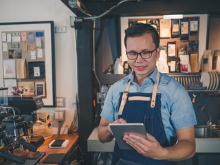 Asian man barista wear blue apron successful small business owner standing at bar counter, Using tablet at coffee shop.
