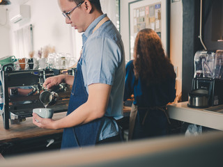 Young asian man barista wear blue apron making cappuccino, Using the coffee machine at the coffee shop.