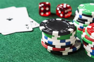 Dice, blackjack cards and stack of poker chips on green felt
