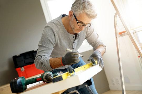 Man at home assembling DIY furniture