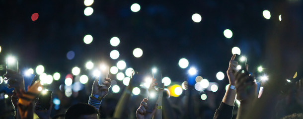 raised hands with smartphone lights during concert - blurred image
