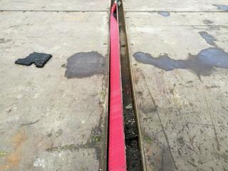 Roter Spanngurt aus Gewebeband auf der alten Holzpritsche eines Lastwagen mit Patina in der Hansestadt Hamburg