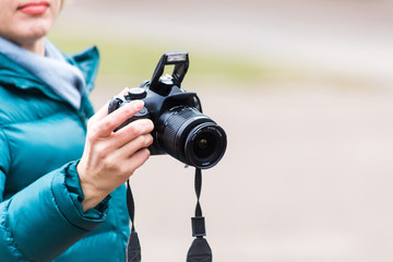 a female hand holds a professional digital SLR camera close-up on a blurred background