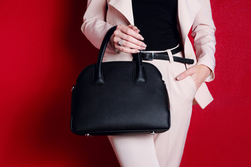 Close up black fashion bag in hand of woman. Female accessory