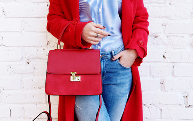 Closeup of red small bag in hand of woman. Spring fashion outfit