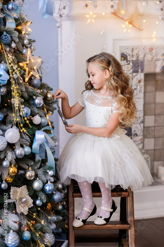 merry christmas celebration beautiful little girl in a amazing dress sitting near the christmas tree