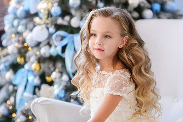 Merry Christmas celebration. Beautiful little girl in a amazing dress sitting near the Christmas tree. Christmas miracles. Happy New Year