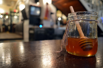 Jar of honey on a wooden table