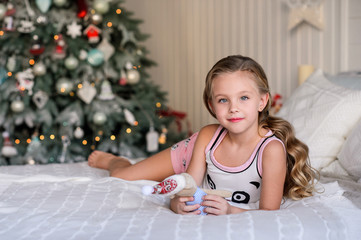 Christmas celebration. Beautiful little girl sitting on a bed  near the Christmas tree. Christmas miracles. Happy New Year