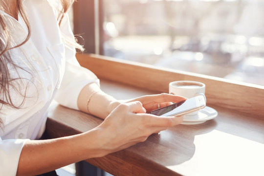 girl in a cafe with a phone and a cup of coffee