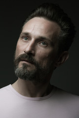Fabulous at any age. Portrait of 40-year-old man standing over dark gray background. Close up. Classic style. Scar on forehead. Model is looking up. Studio shot