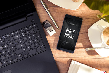 Smartphone with offer of Black Friday lies at the desk