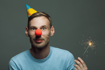 Funny amazed smiling young man in birthday hat with clown nose holding sparkler on grey background. Close up. Studio shot