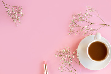 A cup with a coffee or tea on a pink background with a white gypsophila