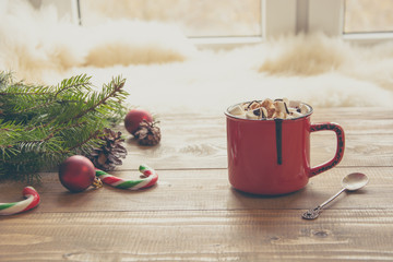 Red cup of hot chocolate with marshmallow on windowsill. Weekend concept. Home style. Christmas time, morning.