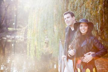 Gourgeous couple walking in autumn park near a lake