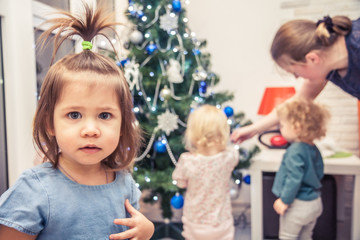 Cute child on the background of family decorating Christms tree in home