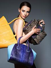 Beautiful naked woman holds fashion handbags