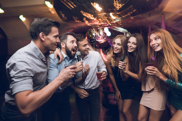 Young people have fun in a nightclub. Three men and three women staged a musical battle.