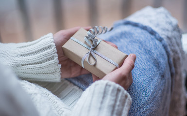Female hands holding beautiful small gift wrapped with satin ribbon