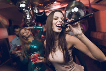 Young people have fun in a nightclub and sing in karaoke. In the foreground is a woman in a beige dress.