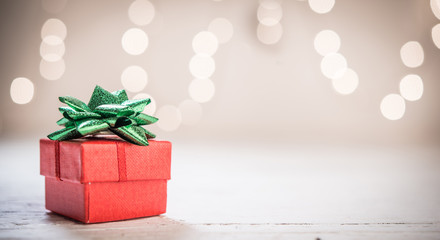 Little red gift box with green ribbon and bokeh light background, copy space