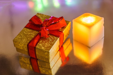 Candle and  gift  box, under colored blurred background.