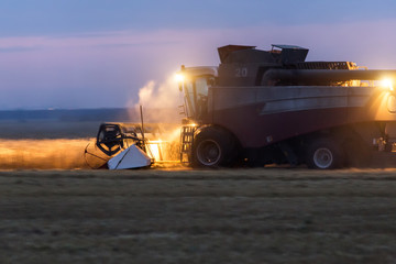 night harvesting in the fields. Combines with lights in motion in the late evening