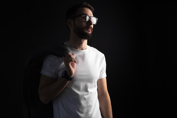 Bearded young hipster in glasses posing with coat in white blank t-shirt on black background