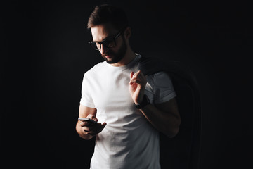 Young bearded man in glasses and coat looks on smartphone in white tshirt. Trendy hipster wearing white blank t-shirt on black background