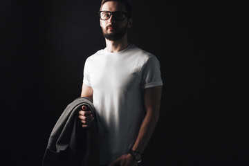 Blank white t-shirt on young bearded businessman standing on a black background. Hipster with a coat and wearing glasses posing in a white tshirt