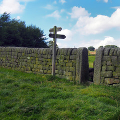 dry stone wall and walking sign in calderdale countryside in west yorkshire