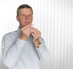 Close up of a tiny modern hearing aid with senior man