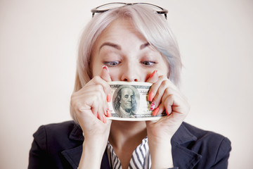 Business Woman covering her mouth with a dollar banknote as symbol of bribery, cheating, financia and l  political  manipulation.