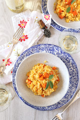 Two plates of pumpkin risotto and glass of white wine